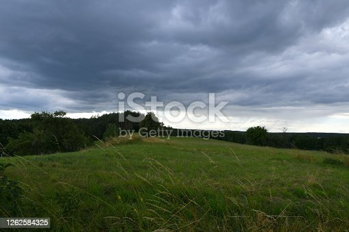 View of a vast pastureland, meadow, or field located next to a dense forest or moor right before a massive storm with dark, heavy, and moody clouds visible above the horizon on a Polish countryside