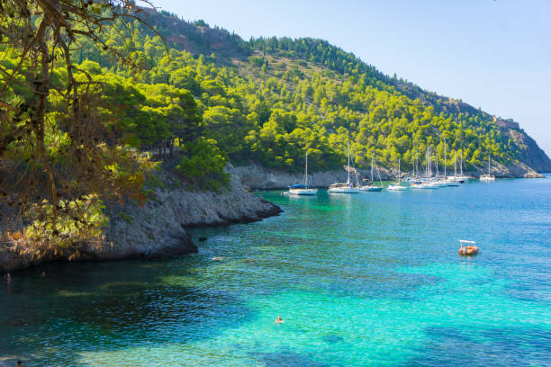 View of a verdant mountain slope and a bay with turquoise sea waters and sailing boats in Assos village, Kefalonia, Greece stock photo