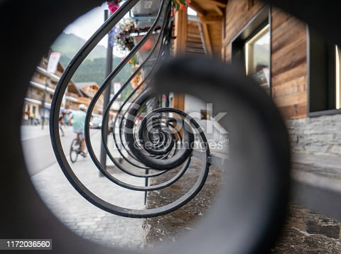 View of a village in Switzerland, looking through an iron logarithmic spiral railing. Traditional wooden chalet style buildings can be seen on the other side of the wide street. A man on a bicycle is riding up the cobbled pathway. The black ironwork runs along the side of a building, below hanging baskets where bright summer flowers have been planted.