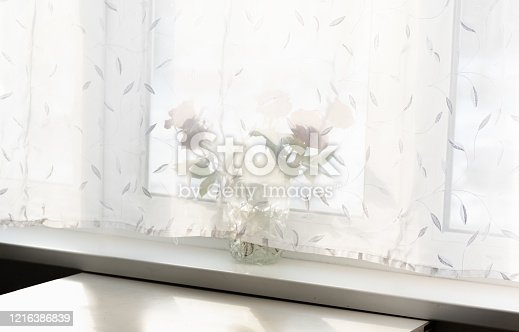 697868238 istock photo view of a window lit by the sun behind a curtain 1216386839