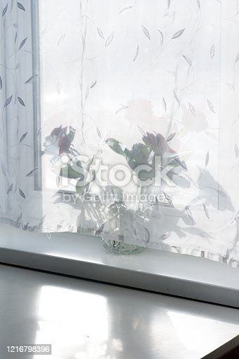 697868238 istock photo view of a window lit by the sun behind a curtain 1216798396