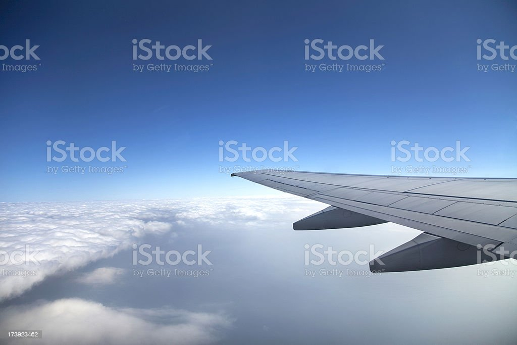 A view of a wing of a jet and the clouds from the inside royalty-free stock photo