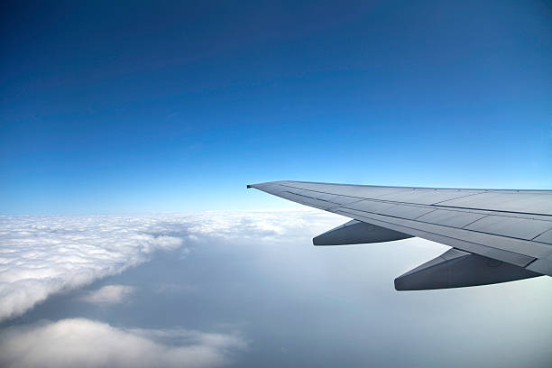 A view of a wing of a jet and the clouds from the inside stock photo