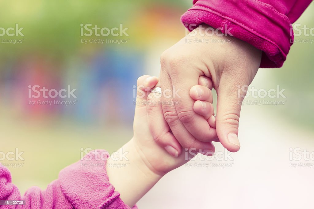 A view of a woman and child's hands holding together. stock photo