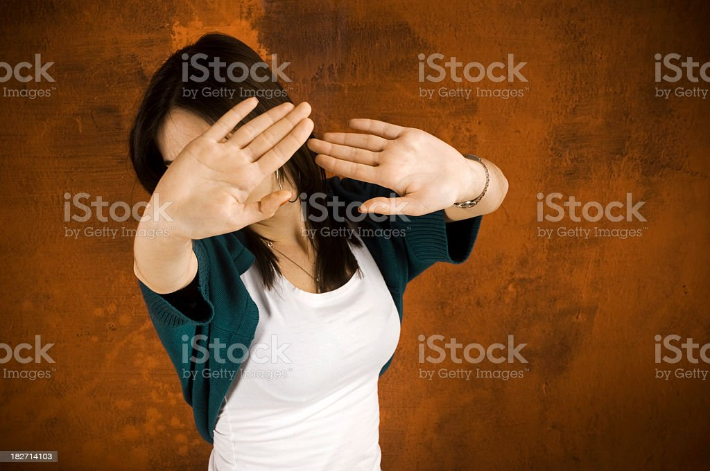 A view of a woman hiding her face from paparazzi stock photo