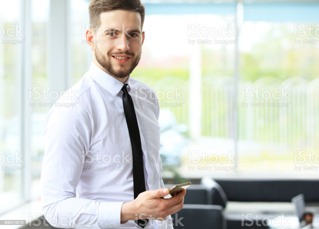 Smartphone kullanarak bir genç çekici iş adamı görünümünü. stok fotoğrafı