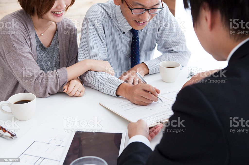 View of a Young attractive couple signing contract stock photo