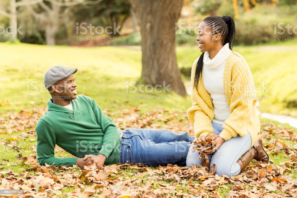 View of a young smiling couple in leaves foto stock royalty-free