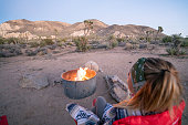 View of a young woman sitting on camping chair enjoying bonfire barbecue in USA.\nOutdoors activity and camping concept.