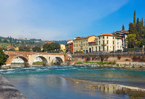 View of Adige river and medieval stone bridge in Verona, Italy. The bridge is free to use. Photo taken from the street.