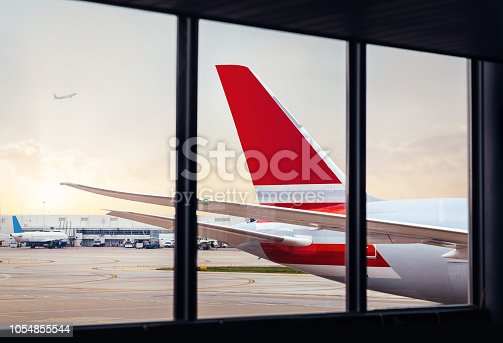 istock View of airplane fuselage tail through window at airport 1054855544