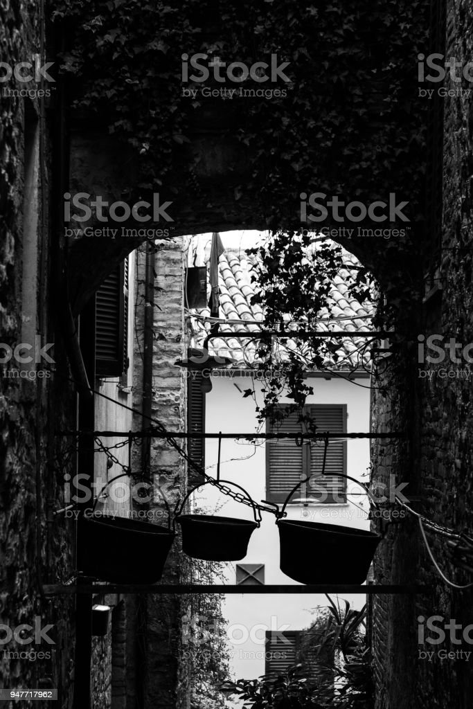 View of an alley in Spello town (Umbria, Italy), with some old copper pots hanging on the rooftop of an arch stock photo