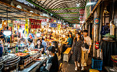 Seoul Korea , 21 September 2019 : View of an alley of the Kwangjang market at night with people eating street food at stalls
