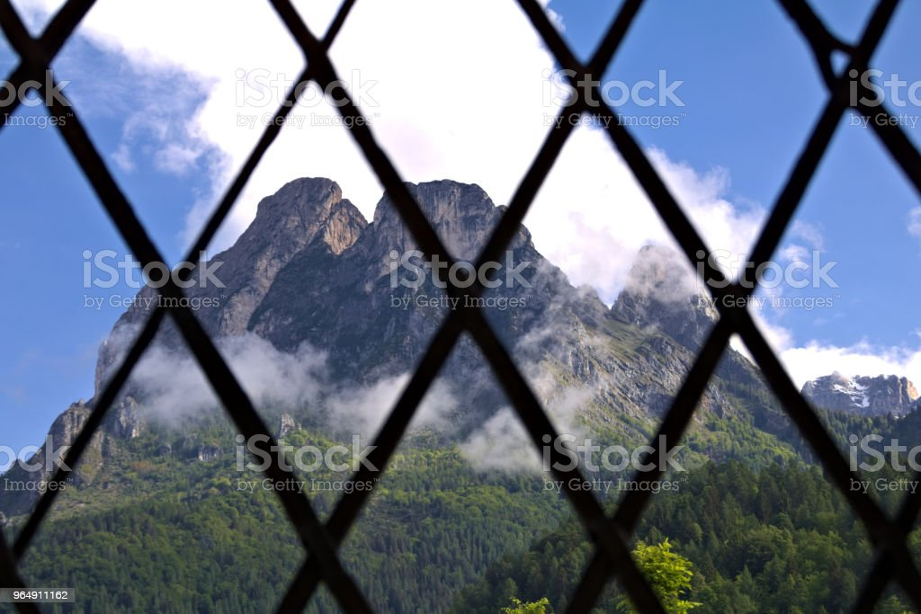 view of an alpine mountain landscape in the dolomites through metal bars royalty-free stock photo