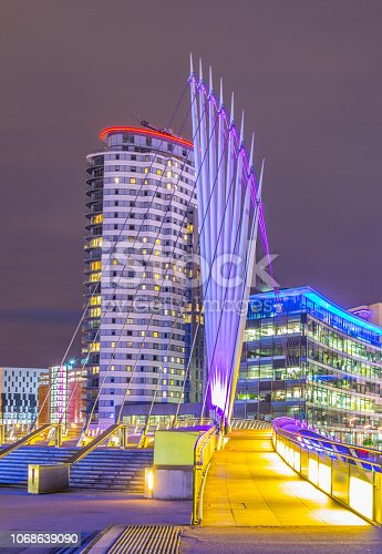View of an illuminated footbridge in Salford quays during night in Manchester, England