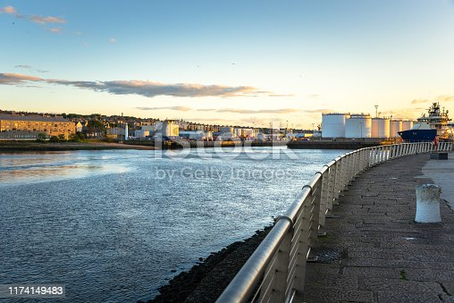View of a commercial port with huge fuel tanks on piers from the footpath along the harbour mouth at sunset. Aberdeen, Scotland, UK.