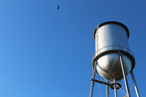 View of an old style water tower against a deep blue sky, horizontal aspect