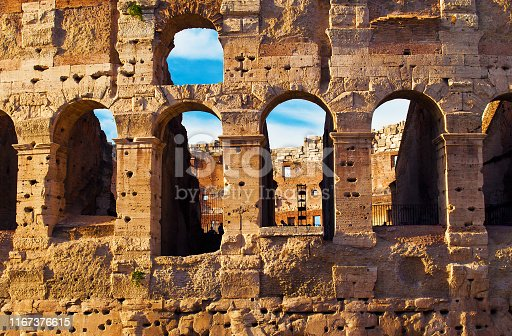 istock View of arches in the amphitheater of Colosseum against blue sky with wispy clouds. Main tourist attraction in old town of Roman empire and Rome, Italy. Sunny autumn day 1167376615