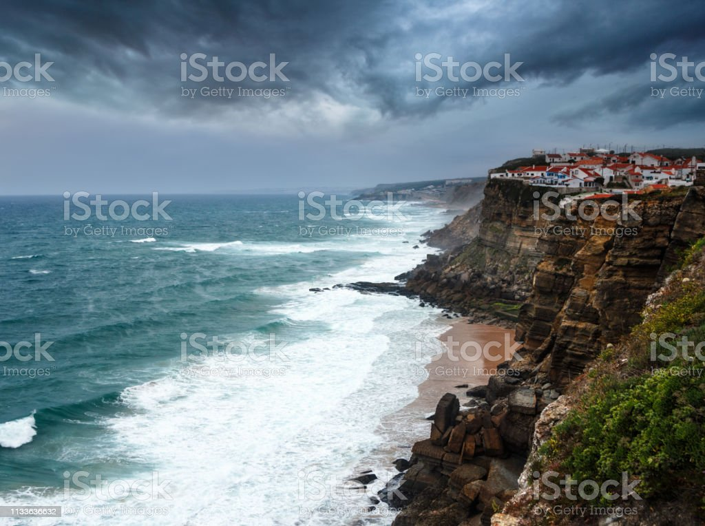 Blick auf Azenhas do Mar Dorf in der Dämmerung. Atlantik vor dem Sturm. Große Wellen stürzen ins felsige Ufer. Dramatischer Blick auf den dunklen, bewölkten Himmel. Sintra. Portugal. – Foto