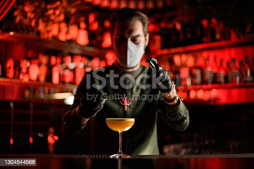 view of bartender in mask and gloves who carefully holds pink flower with tweezers over glass of cocktail and sprinkles on it