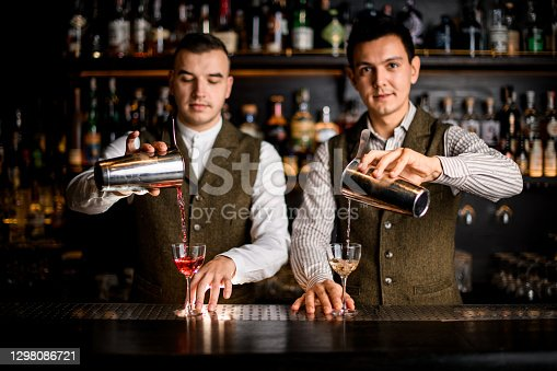 view of two professional male bartenders pouring cocktails into glasses at the same time on the bar counter