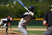 View of baseball batter from behind the catcher as they hit