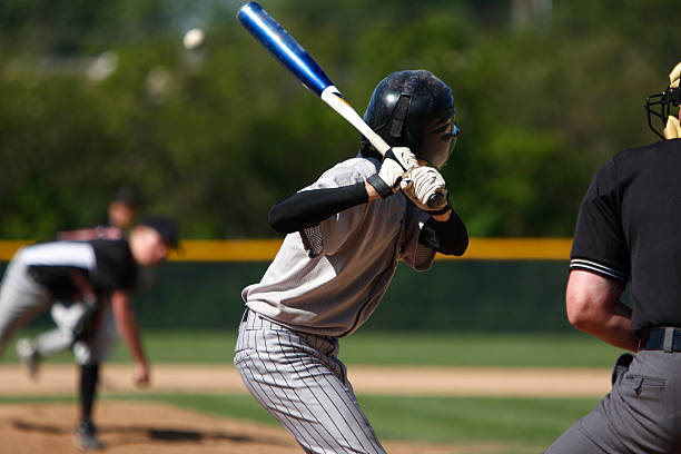 View of baseball batter from behind the catcher as they hit A batter about to hit a pitch during a baseball game. baseball sport stock pictures, royalty-free photos & images