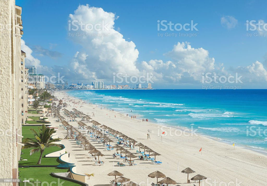 View of beach, Caribbean Sea and clouds in Cancun, Mexico A view along the beach of the Caribbean Sea and hotels in Cancun, Mexico Beach Stock Photo