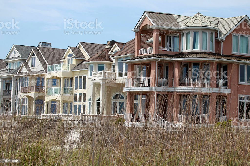View of Beach Homes beyond the dry grass stock photo