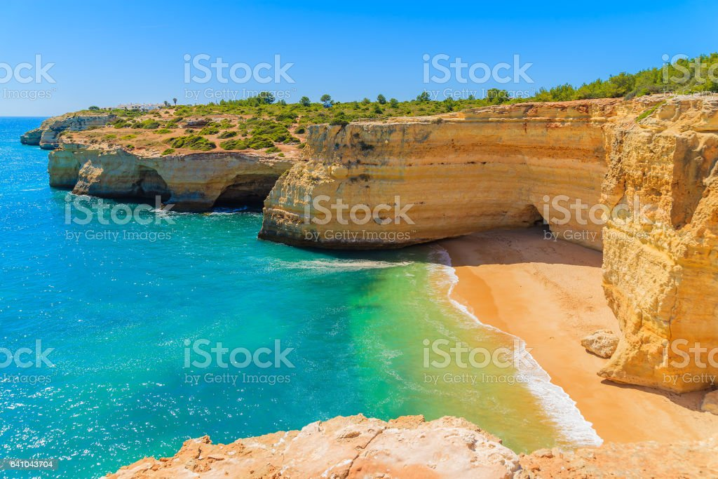 View of beach with golden color cliff rocks near Carvoeiro town, Algarve region, Portugal stock photo