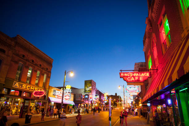 View of Beale Street, Memphis, TN Memphis, TN, USA - June 25, 2017: View of a crowd of tourists enjoying the music clubs and retail establishments that line the famous music district of Beale Street in downtown Memphis, TN at dusk.  Beale Street is on the U.S. National Register of Historic Places. tennessee stock pictures, royalty-free photos & images