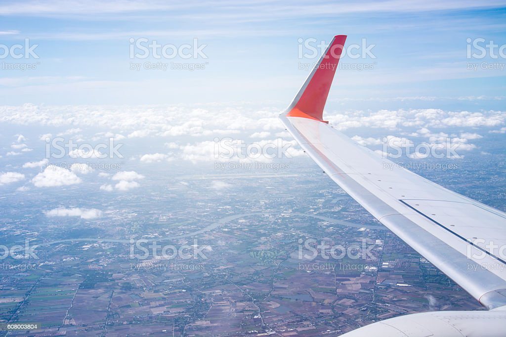 View of beautiful clouds and wing of airplane from window stock photo