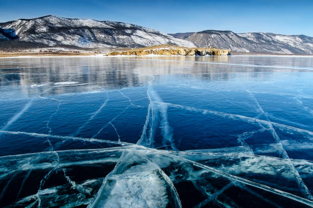 View of beautiful drawings on ice from cracks and bubbles of deep gas on surface of Baikal lake in winter, Russia stock photo