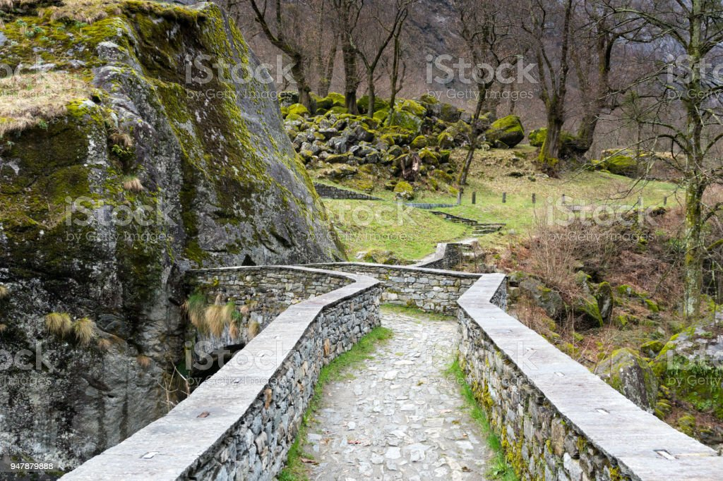 view of beautiful old stone bridge crossing a small mountain stream in a wild and remote alpine valley stock photo
