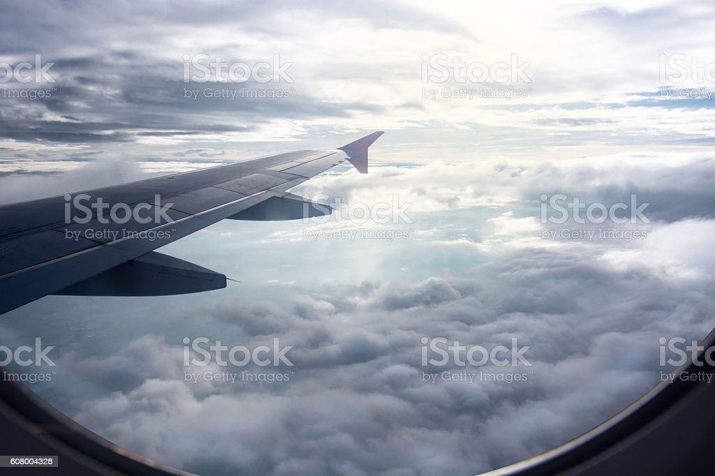 View of beautiful raincloud and wing of airplane from window stock photo