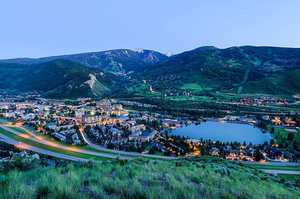 View of Beaver Creek in Summer at Dusk Scenic landscape view showing I-70, the town of Avon, Nottingham Lake and Beaver Creek in the background.  Taken at dusk with glowing lights illuminated in town.  Captured as a 14-bit Raw file. Edited in 16-bit ProPhoto RGB color space. avon colorado stock pictures, royalty-free photos & images