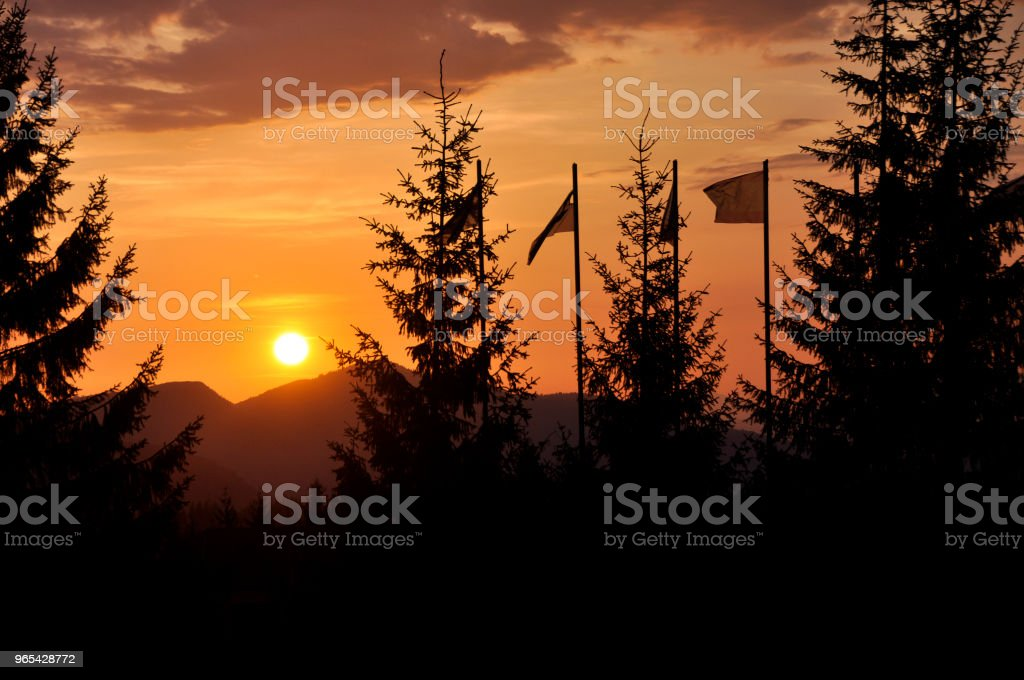 view of big bright white sun in dramatic orange sky over dark mountain range at sunset or sunrise in mountains. Beauty and magnificence of nature. zbiór zdjęć royalty-free
