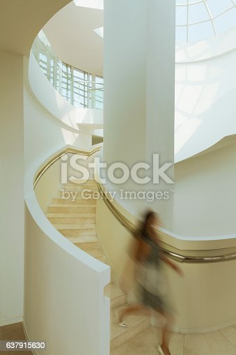 istock View of blurred woman on staircase in modern building atrium 637915630