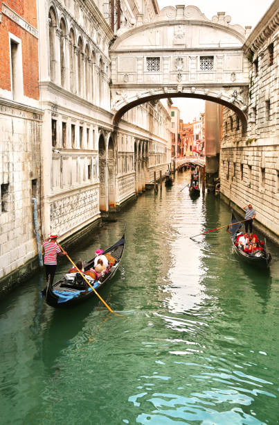 View of bridge of sighs with gondoliers carrying tourists in their gondolas in Venice, italy at sunset stock photo