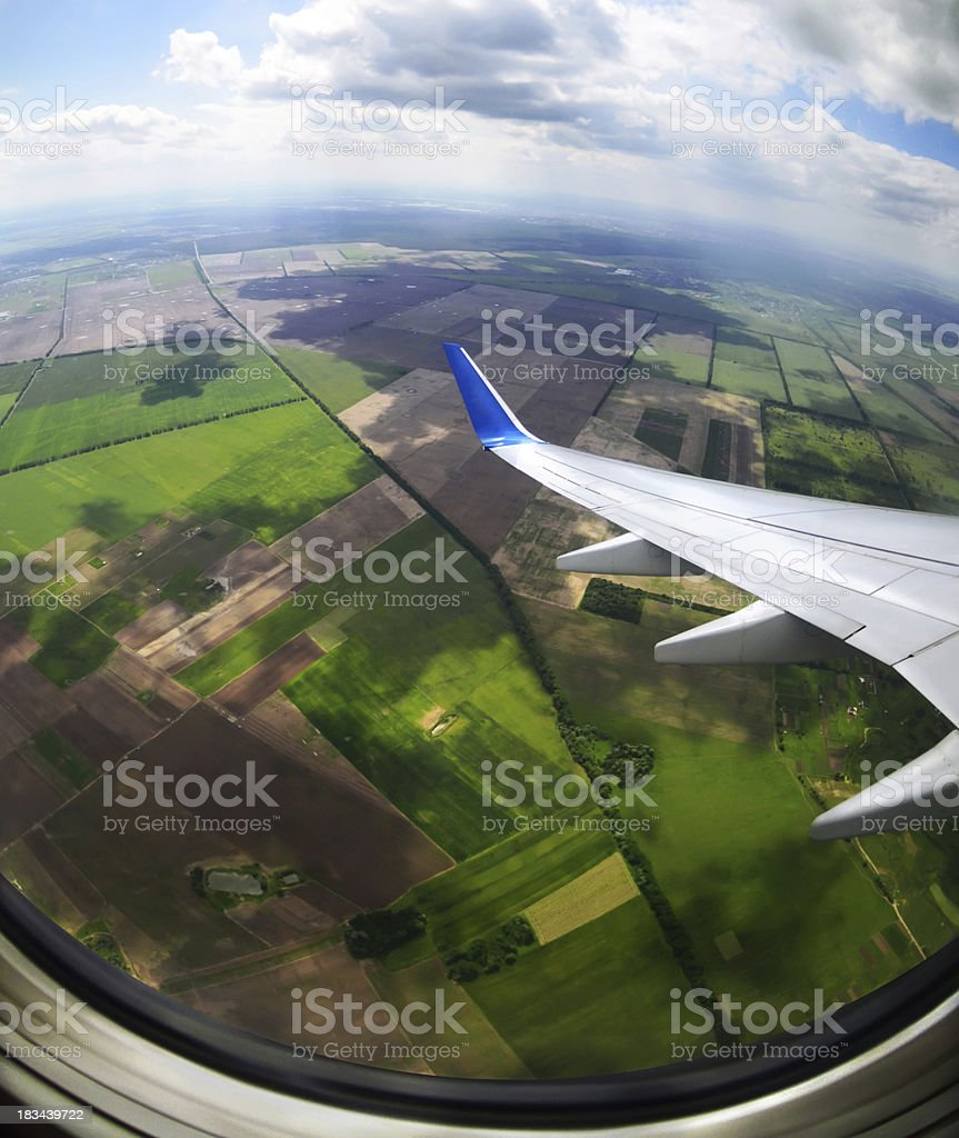 View of brown and green fields from an airplane porthole stock photo