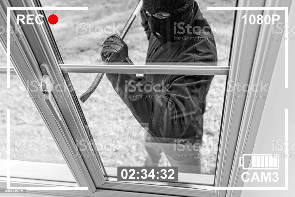 CCTV view of burglar breaking in to home through window stock photo