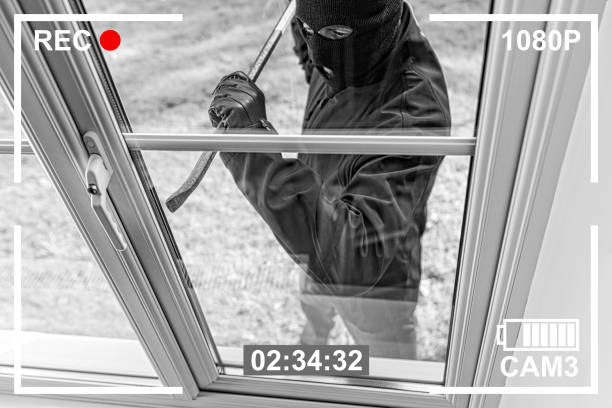 cctv view of burglar breaking in to home through window - thief stock photos and pictures