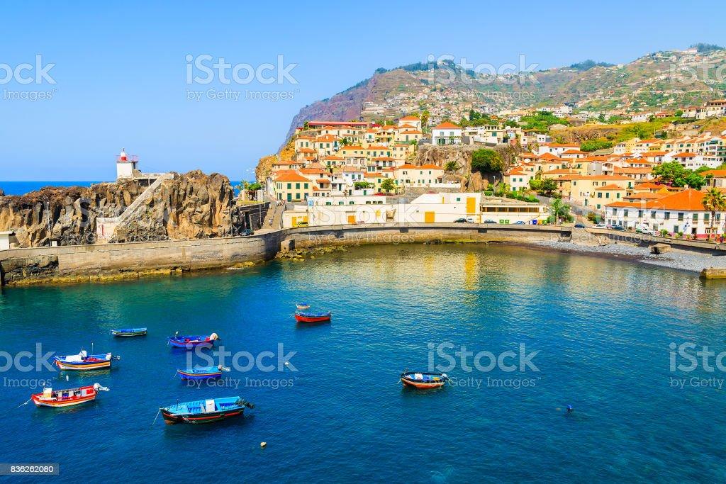 View of Camara de Lobos port with colourful fishing boats on sea, Madeira island