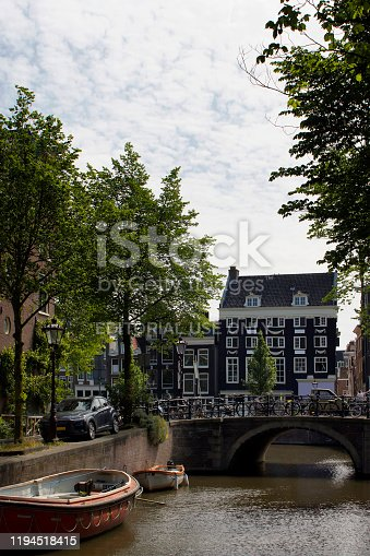 825525754 istock photo View of canal, parked boats and bicycles, trees, stone bridge, historical, traditional and typical building showing the lifestyle in Amsterdam. It is a sunny summer day. 1194518415