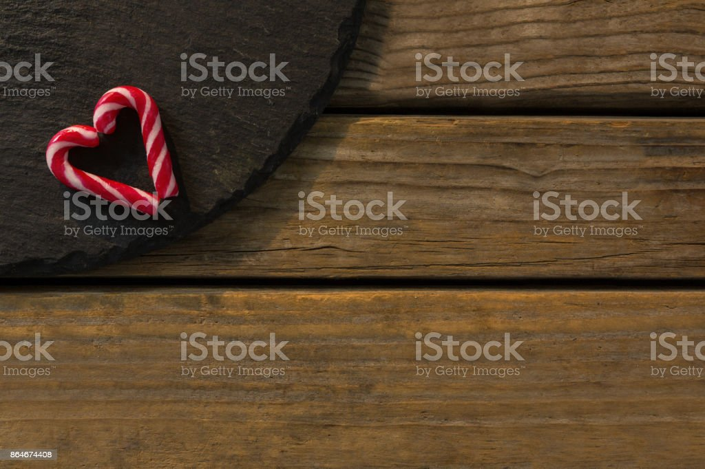 View of candy cane arranged in heart shape on wood stock photo