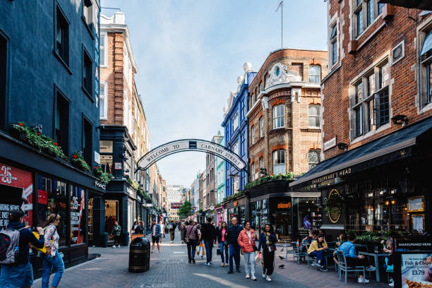 View of Carnaby Street. It is a pedestrianised shopping street in Soho in London London, UK - May 15, 2019: View of Carnaby Street. It is a pedestrianised shopping street in Soho in the City of Westminster. Welcome to Carnaby Street sign carnaby street stock pictures, royalty-free photos & images