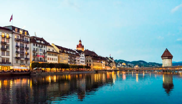 view of chapel bridge on river reuss with lucerne city skyline at sunset in switzerland - lucerne stock pictures, royalty-free photos & images