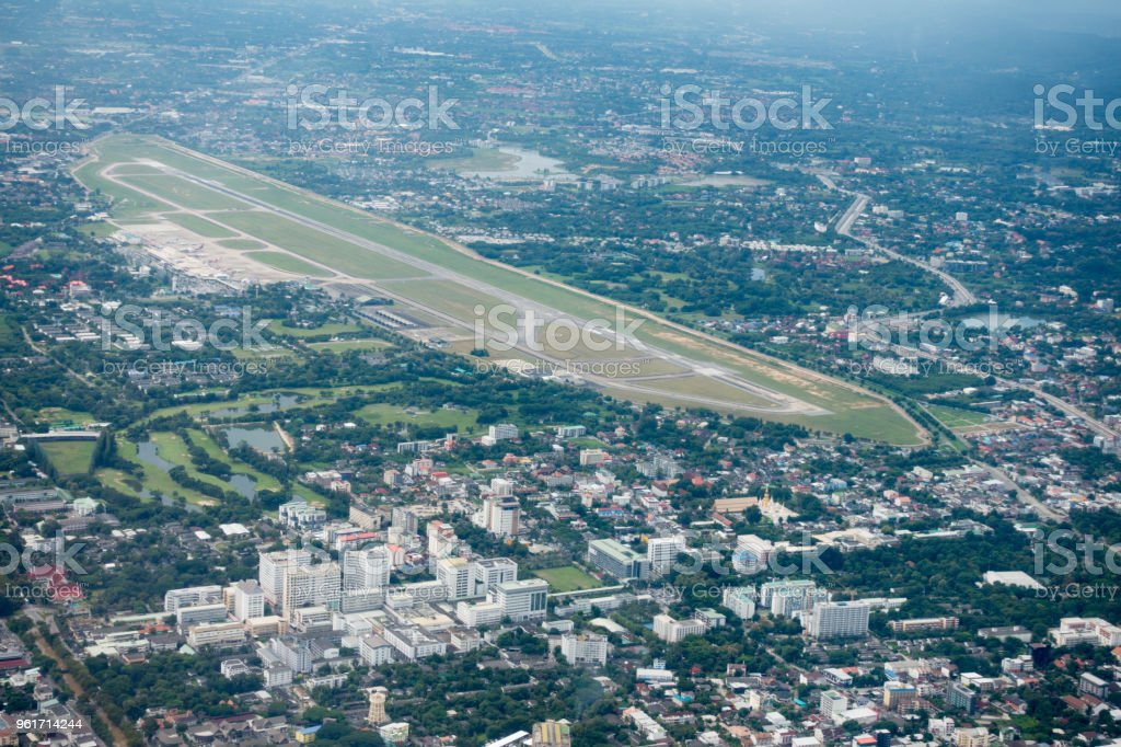 View of Chiangmai City and Chiangmai international airport (CNX) Under Light Through the Clouds , Aerial View from Airplane. stock photo