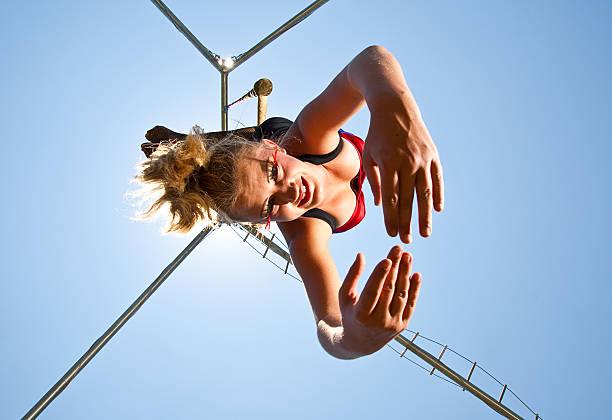 zirkus-akrobaten hängen upsidedown - trapez stock-fotos und bilder
