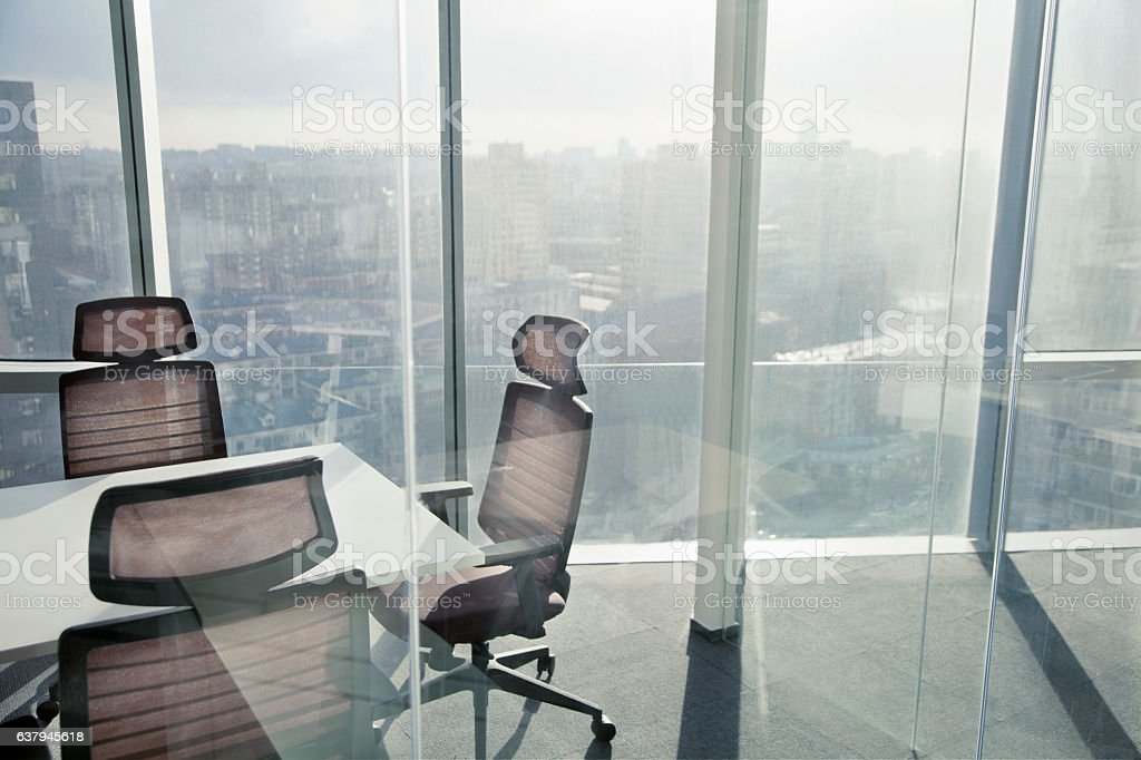 View of city with sunlight through window in meeting room stock photo